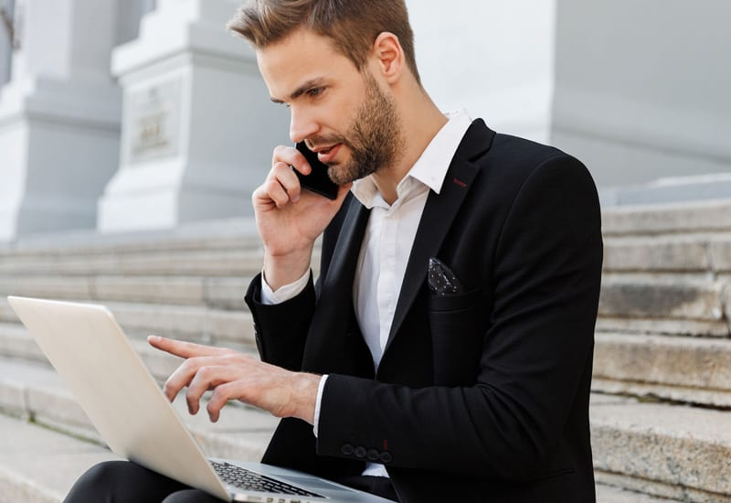 Businessman sitting on the steps of a government building on phone using laptop